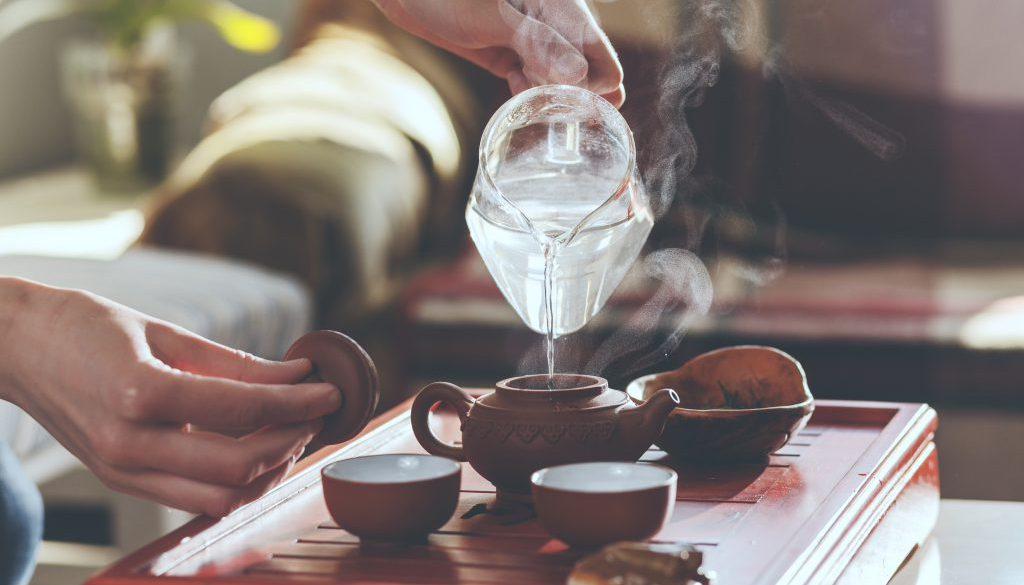 The tea ceremony. The woman pours hot water into the teapot