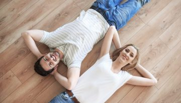Couple with hands behind head laying on the floor